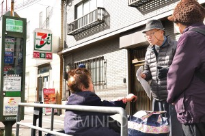 停留所で市バスを待つ利用者に署名を訴える「大阪市営交通を守る市民連絡会」の稲垣さん=6日、大阪市淀川区内