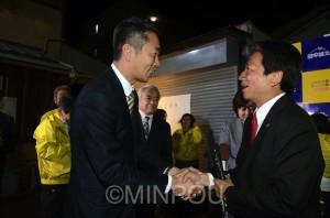 八尾市長選で当選した田中誠太氏(右)と握手する清水忠史衆院議員=4月26日、八尾市内