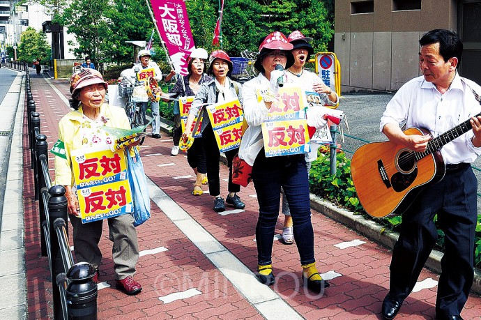 下町の路地裏や大型商業施設でにぎわう上本町駅周辺などをギター伴奏に合わせて「守ろう大阪」を歌いながら路地裏を練り歩いて大阪市廃止・分割「反対」を訴える天王寺区の日本共産党員たち。道行く市民が「僕も反対。大阪市なくすなんて駄目」などと声援を送りました=15日、天王寺区内