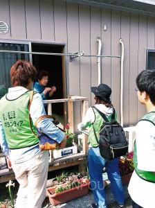 小高区の牛越仮設住宅住民に聞き取りをするボランティア参加者=3日、南相馬市内