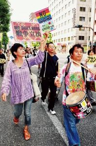 SADLのドラム隊と一緒にプラカードを掲げてパレードする参加者=7日、大阪市北区内