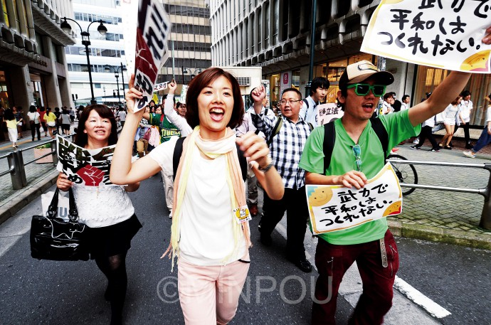 若者憲法集会が呼び掛けた「戦争法案反対」の渋谷デモには3500人が参加し、繁華街にあふれる市民の注目を集めました。大阪の若者たちと一緒に「絶対反対」とコールするわたなべ候補=14日、東京都渋谷区内