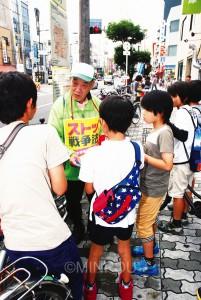 戦争法案反対署名行動で、子どもたちと対話する男性=6日、大阪市西成区内