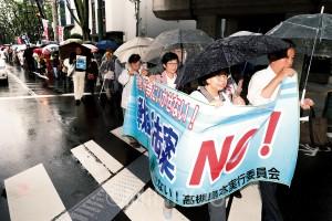 「私たちの力で戦争法案を止める」と、雨の中を歩いてアピールする宮原府議ら(右端)=4日、高槻市内