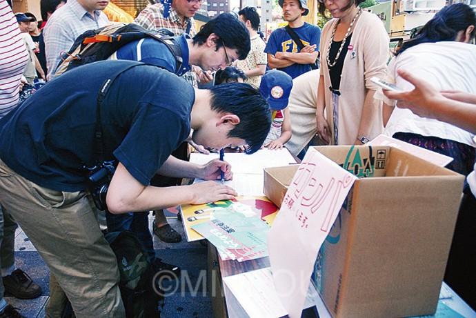 「戦争法案」廃案を求める衆院議員宛ての要請書を書く青年ら=12日、大阪市中央区内