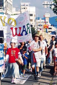 参加者が寄せ書きした横断幕を先頭にデモする市民=23日、岸和田市内