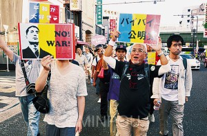 プラカードを手にデモ行進する春村さん(右端)=23日、大阪市中央区内