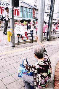 「ママの会@池田」のパレードに、沿道からこぶしを上げて声援する人も=18日、池田市内