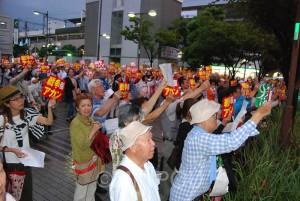 「戦争アカン」のステッカーを掲げながら「安倍と一緒の市政はいらない」とコールする市民=6日、東大阪市内