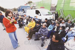 約300人が参加した米軍キャンプ・シュワブゲート前での抗議集会で連帯あいさつするわたなべ氏(左)=17日、沖縄県名護市内