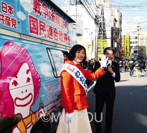 「結ワゴン」の前で辰巳議員と訴えるわたなべさん=11日、大阪市浪速区内