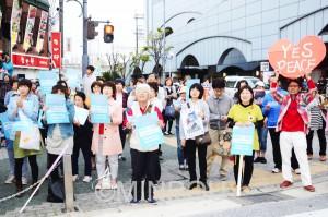 泉州サウンドDEMOの街頭演説でスピーチに声援を送る人たち=4月24日、岸和田市内