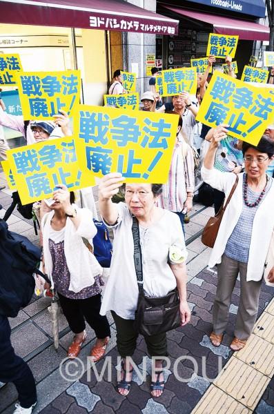 「戦争法は廃止」のプラカードを掲げる参加者=19日、大阪市北区内
