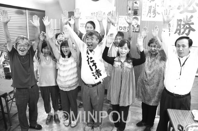 当選の一報を受けバンザイする力武氏と支援者ら=9月25日、河南町内