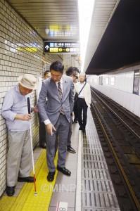 視覚障害者にとって「欄干のない橋」と変わらない駅ホーム。御堂筋線と四ツ橋線が合流し、危険度の高い大国町駅を視察する清水衆院議員ら=3日、大阪市浪速区内