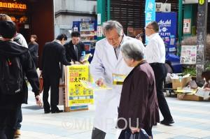 医師の呼び掛けに負担増・対象外しの中止を求める署名に応じる人々=22日、大阪市都島区内