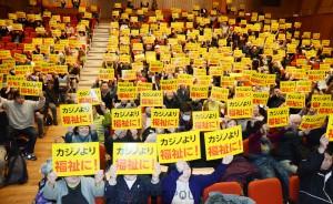 「カジノより福祉に!」のプラカードを掲げてアピールする集会参加者=19日、大阪市阿倍野区内