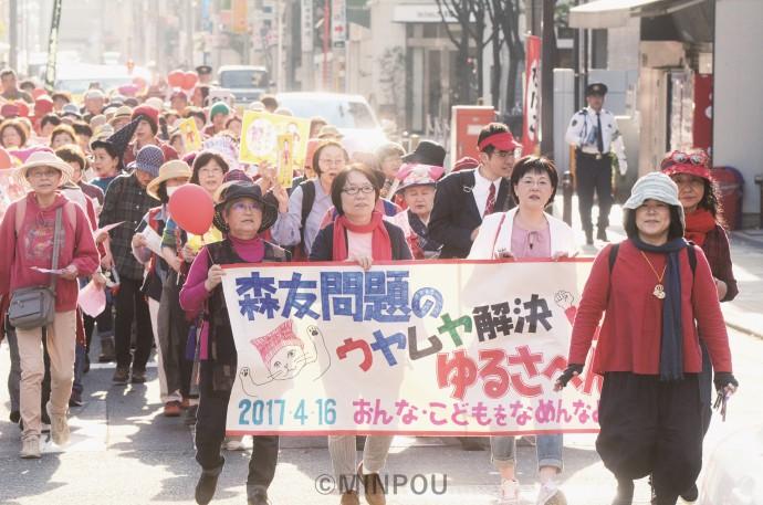「森友問題、真相究明」「松井知事は責任果たせ」「教育勅語と愛国心、アベ政治は危険です」と唱和しながらパレードする人たち=16日、大阪市中央区内