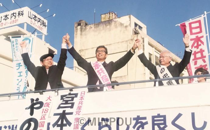 聴衆に向かって手を上げる、左から新川氏、宮本氏、やの氏=4月23日、和泉市内