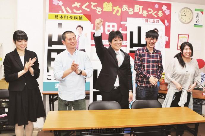 初当選を決め支持者の歓声に応えてガッツポーズする山田さん(中央)=16日、島本町内