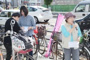 住吉市民病院を充実させる市民の会の署名に応じる親子=8日、大阪市西成区内
