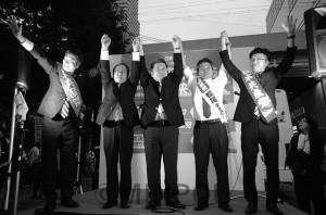 京橋駅前の街頭演説で、日本共産党の小池晃書記局長、予定候補者と声援に応えて手を取り合う村上氏(左から2人目)=10月7日、大阪市都島区内