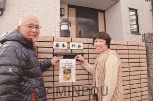 自宅の郵便ポストに「3千万署名」の投函を呼び掛けるステッカーを張る仲谷さん(右)と林事務局長=11日、羽曳野市内