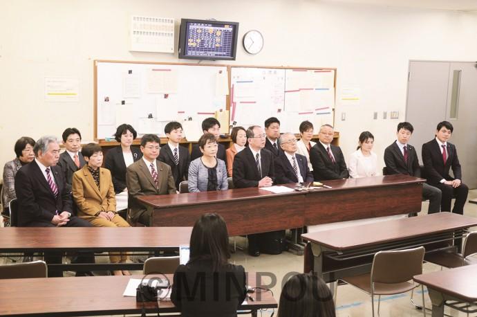 記者会見に臨む日本共産党の柳府委員長(前列中央)と大阪市議候補17氏=2月23日、大阪市役所内
