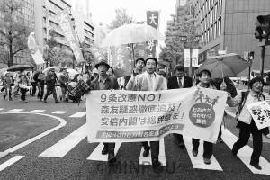 内閣退陣をとデモ行進する、山下よしき参院議員(前列中央)ら=14日、大阪市中央区内