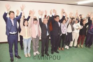 支援者とバンザイする高道(中央右)、福岡(同左)の両氏。左端は清水忠史前衆院議員=13日、泉佐野市内
