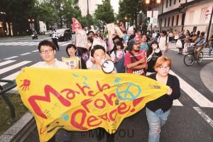 手作りの横断幕を先頭にラップ音楽に合わせたコールで「9条守れ、平和が一番」「戦争したがる総理はいらない」とアピールしました=5月27日、大阪市中央区内