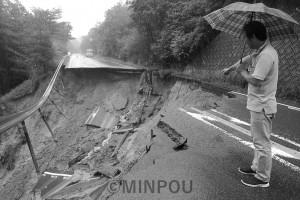 山から谷への土砂崩れが起き、約30メートルにわたって寸断された国道173号線。見ているのは中西能勢町議=6日、能勢町内
