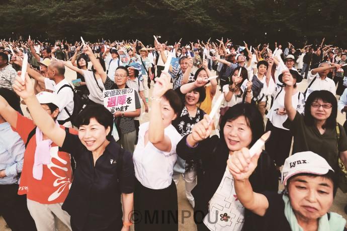 キャンドル型ペンライトを手に、「終戦協定を実現し南北統一を」とコールする人たち=7月27日、大阪市西区内