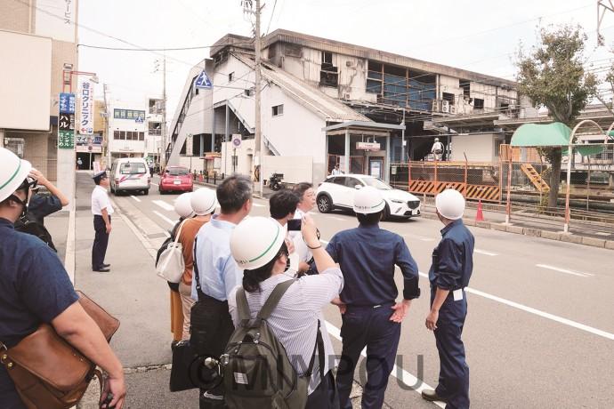 火災が起きた南海尾崎駅で焼失した駅舎や復旧状況を視察する一行ら=7日、阪南市内