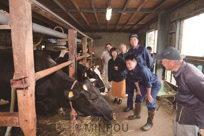 酪農家の北川さん(右端)から停電による酪農の被害状況を聞く山下、たつみ、北村の各氏ら=7日、熊取町内