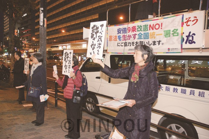 緊急宣伝で「アベ政治許さない」のプラカードを掲げて宣伝する人たち=10日、大阪市天王寺区内