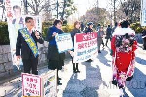 成人式の式典会場に向かう新成人に、「国民が主人公の政治をつくりましょう」と呼び掛ける、日本共産党のうち海公仁府議候補(東大阪市区)と東大阪市議ら=14日、東大阪市内