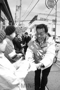 清水氏と共に市民と握手を交わす小松候補=16日、八尾市内