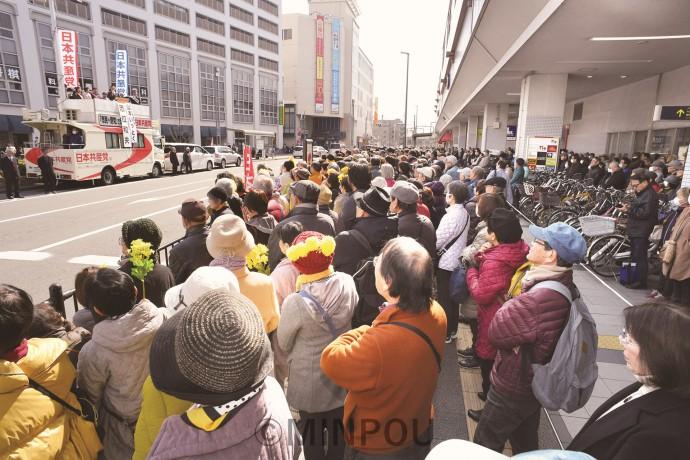 阪急曽根駅前で志位委員長の演説を聞く人たち=2月24日、豊中市内