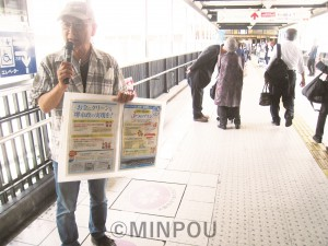 ボードに張り付けた「つくる会」ビラを手にマイクで訴える市民=21日、堺市南区内