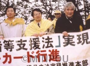 被災者支援法実現へデモ行進する(右から)小田実さん、緒方靖夫さん(現日本共産党副委員長)、山下さん=1998年3月、東京都内