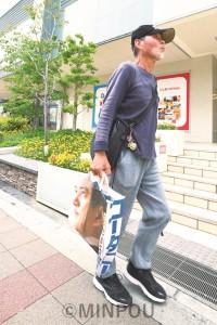 手作りバッグを手に歩き続ける井上将臣さん=20日、大阪市阿倍野区内