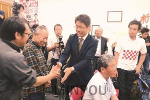 開票結果を受け支援者一人一人と握手を交わす野村友昭氏=9日、堺市堺区内