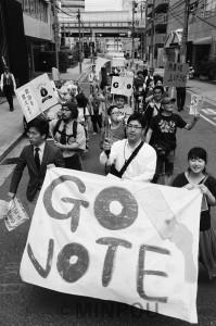 「選挙に行って政治を変えよう」とアピールする大阪若者憲法集会実行委員会のパレード=23日、大阪市中央区内