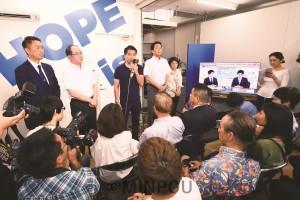 選挙結果を受け、支援者らにあいさつする辰巳氏(正面左から3人目)=21日、大阪市中央区内