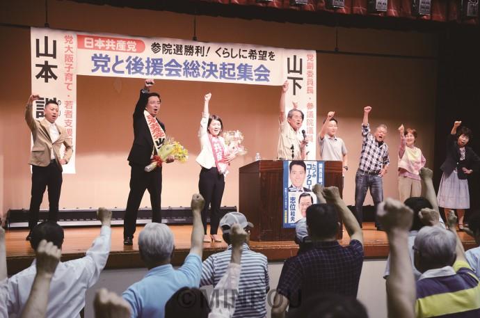 大阪二区地区委員会が参院選勝利に向けて開いた総決起集会で、参加者と共に決意を固め合う、山下よしき副委員長(舞台上左から2人目)、山本のりこ比例候補(同3人目)=6月19日、大阪市平野区内