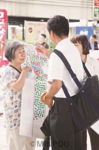 夢洲カジノ万博の賛否を問うシールアンケートをする人たち=8月30日、大阪市都島区内
