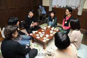 子育て世代の人らと懇談する小川氏(左から3人目)=2月11日、大阪市中央区内