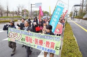「子どもの貧困をなくせ」など唱和し府庁周囲をデモ行進しました=2月25日、大阪市中央区内