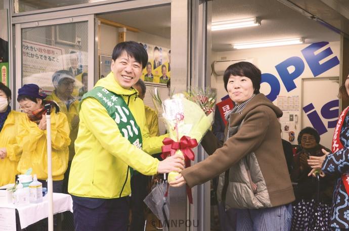 事務所開きで新婦人中央支部内後援会「アトム倶楽部」の花束を受ける小川氏(左)=2月22日、大阪市中央区内